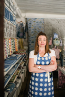 Portrait of confident woman standing with arms crossed in fabric shop 11081011381| 写真素材・ストックフォト・画像・イラスト素材|アマナイメージズ