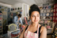 Confident smiling woman looking away while colleague working in shop