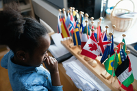 High angle view of thoughtful girl looking at various flags in classroom 11081011464| 写真素材・ストックフォト・画像・イラスト素材|アマナイメージズ
