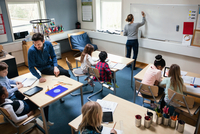 High angle view of female teacher writing on board while male educator sitting with students at desk in classroom 11081011521| 写真素材・ストックフォト・画像・イラスト素材|アマナイメージズ