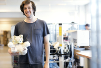 Portrait of smiling man holding teddy bear while standing at workshop 11081011561| 写真素材・ストックフォト・画像・イラスト素材|アマナイメージズ