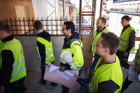 Side view of manger holding blue prints walking with manual workers at construction site