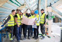 Manager standing with manual workers while reading blue prints at construction site 11081011680| 写真素材・ストックフォト・画像・イラスト素材|アマナイメージズ