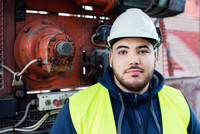 Portrait of confident manual worker standing against machinery in industry