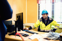 Smiling construction worker in protective wear talking to man while sitting at desk 11081011718| 写真素材・ストックフォト・画像・イラスト素材|アマナイメージズ