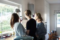 Woman taking selfie while standing with family in kitchen at new home 11081011727| 写真素材・ストックフォト・画像・イラスト素材|アマナイメージズ