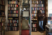 Portrait of confident man with arms crossed standing in library 11081011923| 写真素材・ストックフォト・画像・イラスト素材|アマナイメージズ