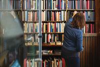 Rear view of librarian arranging books on shelf in antique shop 11081011935| 写真素材・ストックフォト・画像・イラスト素材|アマナイメージズ