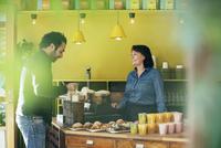 Happy waitress looking at male customer adding sugar in coffee 11081011992| 写真素材・ストックフォト・画像・イラスト素材|アマナイメージズ