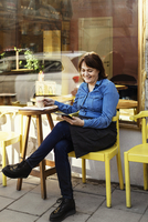 Happy owner using digital tablet while sitting at sidewalk cafe 11081011999  写真素材・ストックフォト・画像・イラスト素材 アマナイメージズ