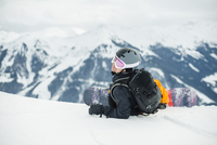 Man with snowboard relaxing against snowcapped mountains 11081012001| 写真素材・ストックフォト・画像・イラスト素材|アマナイメージズ