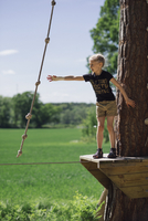 Girl trying to hold rope while standing on wood