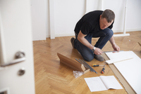 Full length of male carpenter working while reading manual at home 11081012052| 写真素材・ストックフォト・画像・イラスト素材|アマナイメージズ