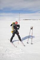 Full length of mature female skier inserting pole in snow