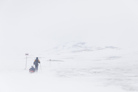 Rear view of man pulling luggage on snow covered mountain 11081012081| 写真素材・ストックフォト・画像・イラスト素材|アマナイメージズ