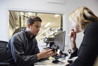 Male owner showing spare part to female customer in office 11081012096| 写真素材・ストックフォト・画像・イラスト素材|アマナイメージズ