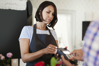 Serious female owner holding credit card reader for customer