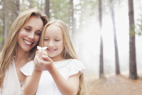 Smiling mother and daughter holding butterfly in woods