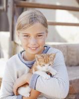 Portrait of smiling girl holding kitten 11086000315| 写真素材・ストックフォト・画像・イラスト素材|アマナイメージズ
