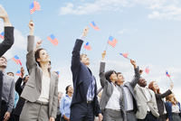 Smiling business people in crowd waving American flags