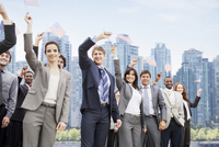 Portrait of smiling business people waving American flags