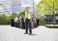 Portrait of smiling construction worker with business people