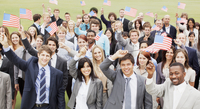 Portrait of smiling business people waving American flags ov