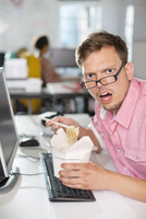Businessman eating Chinese food at desk