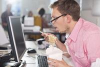 Businessman eating Chinese food at desk 11086001844| 写真素材・ストックフォト・画像・イラスト素材|アマナイメージズ