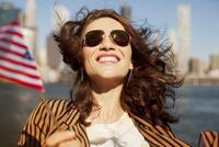 Smiling woman waving American flag 11086001902| 写真素材・ストックフォト・画像・イラスト素材|アマナイメージズ