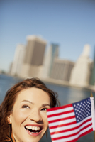 Woman waving American flag by city cityscape