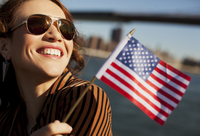 Woman waving American flag by urban bridge