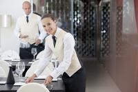 Waitress setting table in restaurant 11086002217| 写真素材・ストックフォト・画像・イラスト素材|アマナイメージズ
