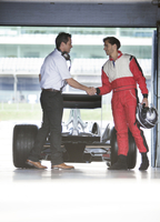 Racer and manager shaking hands in garage