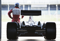Racer standing with car in garage