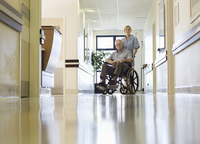 Nurse wheeling older patient in hospital