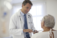 Doctor talking to older patient in hospital