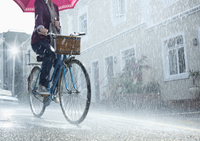 Woman riding bicycle with umbrella in rainy street