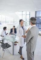Doctor and businessman shaking hands in meeting