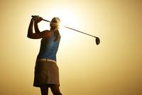 Sun shining behind woman swinging golf club 11086008177| 写真素材・ストックフォト・画像・イラスト素材|アマナイメージズ