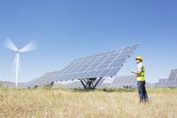 Worker examining solar panels in rural landscape 11086009726  写真素材・ストックフォト・画像・イラスト素材 アマナイメージズ
