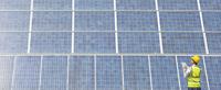 Worker examining solar panel in rural landscape 11086009739  写真素材・ストックフォト・画像・イラスト素材 アマナイメージズ