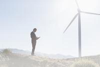 Businessman using laptop by wind turbine in rural landscape