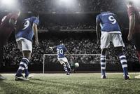 Soccer player kicking ball at goal