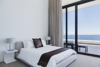 Bed and lamps in modern bedroom overlooking ocean