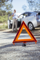 Man talking on cell phone at roadside behind warning triangle