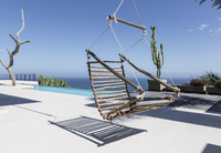 Hanging wooden chair on luxury patio overlooking ocean