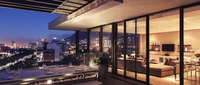 Illuminated modern living room and patio overlooking city
