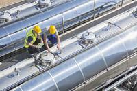 Workers on platform above stainless steel milk tanker 11086013259| 写真素材・ストックフォト・画像・イラスト素材|アマナイメージズ