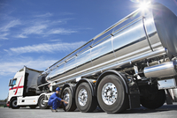 Worker checking tire on stainless steel milk tanker 11086013297| 写真素材・ストックフォト・画像・イラスト素材|アマナイメージズ